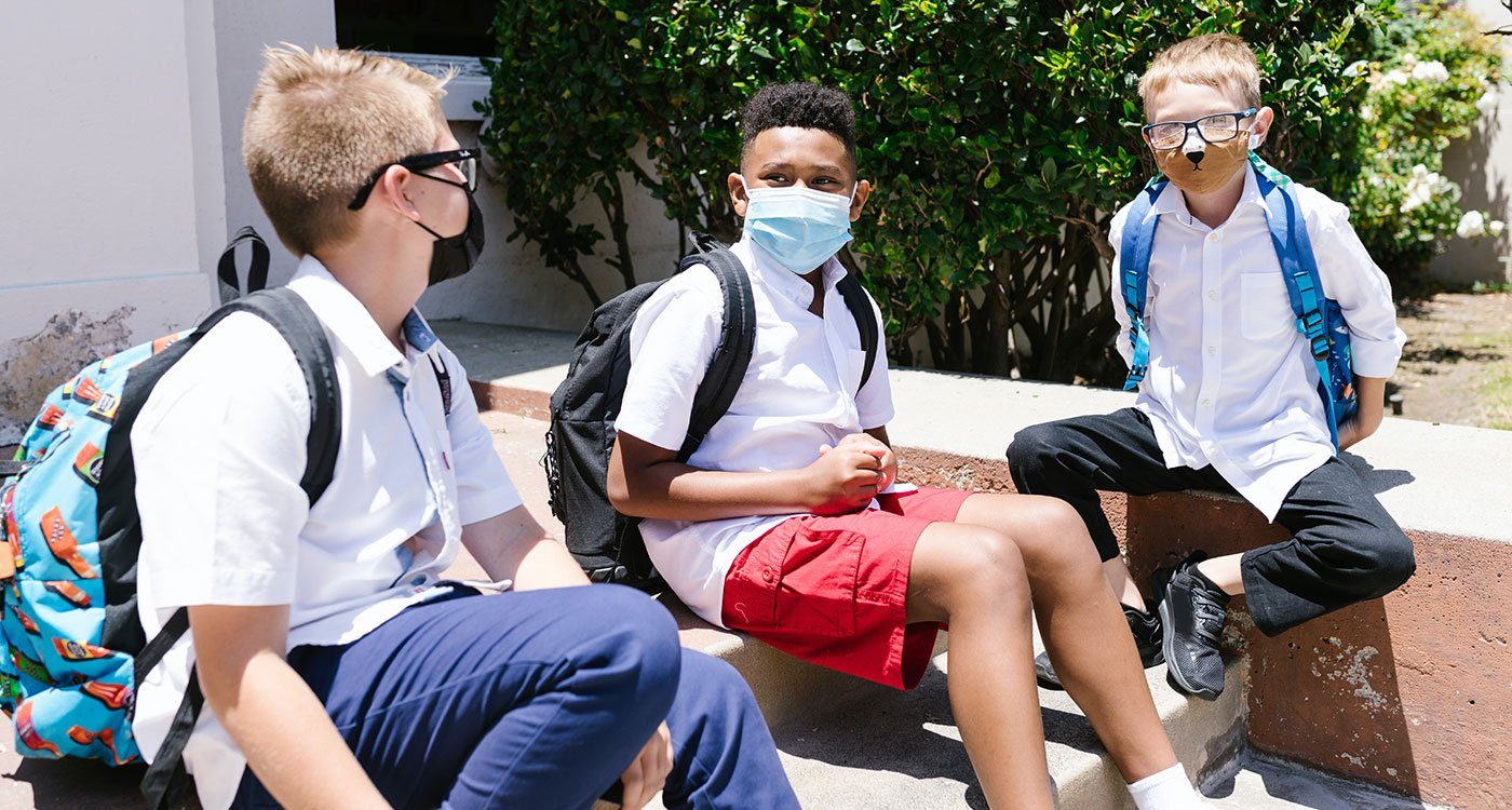 School boys sitting together with masks on