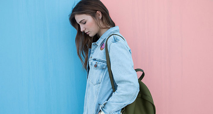 Teenage girl walking with backpack looking sad