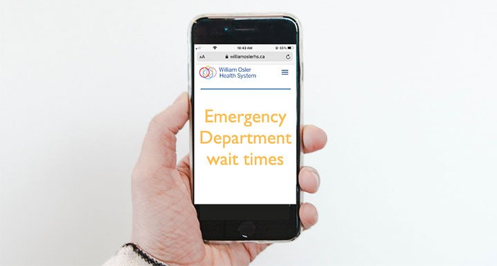 Hand holding cell phone showing the Emergency Department wait clocks webpage
