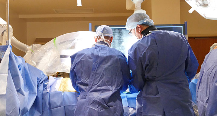 Two physicians performing surgery on a patient