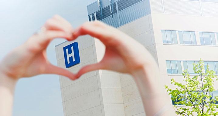 Heart hands around hospital sign