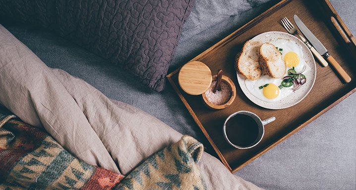 A tray of breakfast food and coffee on top of a bed