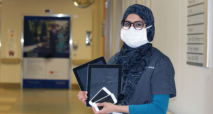 Dr. Humaira Saeed holding digital devices used for virtual visitation